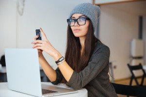 fata bruneta cu ochelari, fes si telefon in mana in fata laptopului