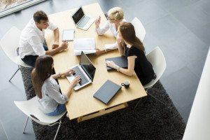 patru oameni care stau la birou