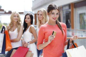 patru fete cu sacose de cumparaturi in mana