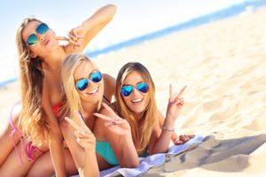trei fete fericite pe plaja zambind