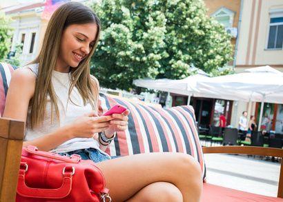 fata blonda care foloseste telefonul mobil roz